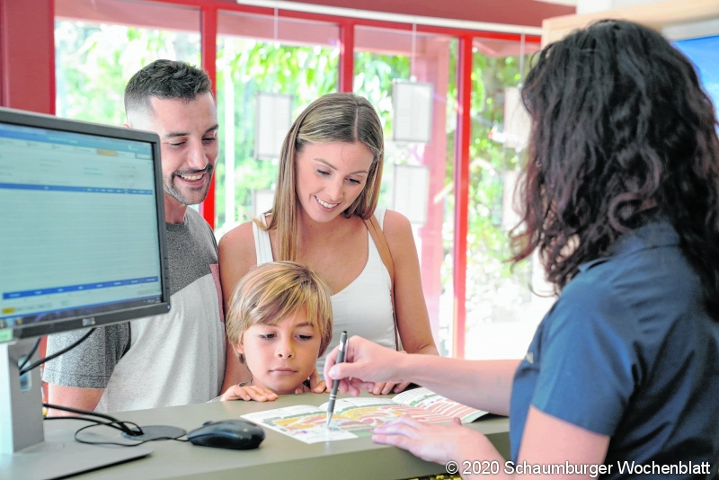 Family checking-in at hotel reception desk